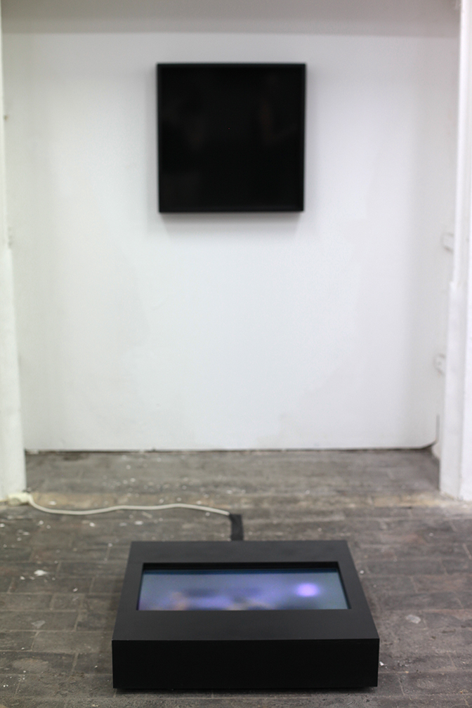 A hidden camera behind the black box on the wall projects a light portrait of the person standing in front of it, rendering them indistinguishable.